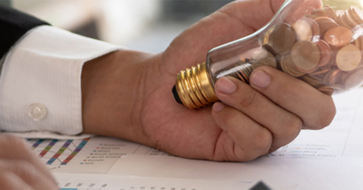 Hand holding a lightbulb with coins inside.